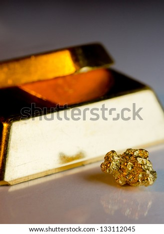 Close-up of fine gold ingots and a gold-nugget - stock photo