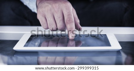 Close up of finger from man touching tablet in bright living room
