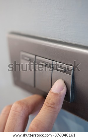Close up of finger is turning on or off light switch. Copy space.