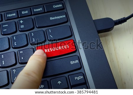 Close up of finger on keyboard button with RESOURCES word - stock photo