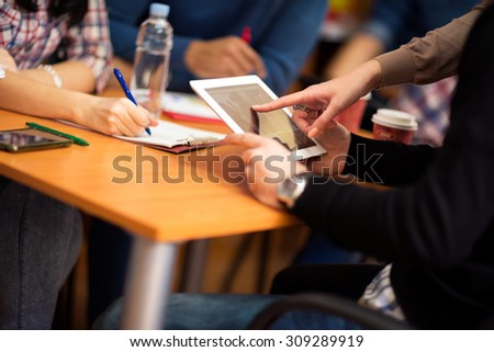 Close up of finger pointing on touch screen tablet device - stock photo