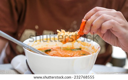 Close up of fingers holding peel shrimp from tom yum hot and spicy thai food   - stock photo