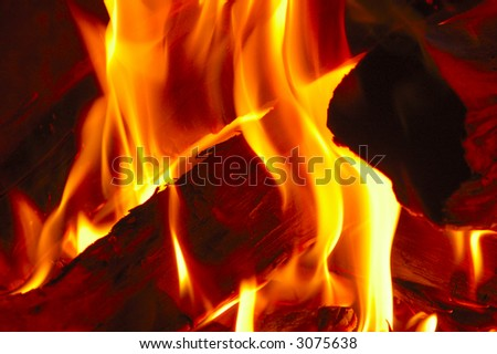 Close-up of fire burning on the logs in a fireplace. - stock photo