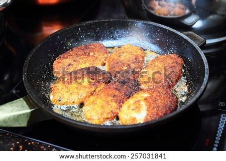 Close up of fish cutlets preparation on frying pan - stock photo
