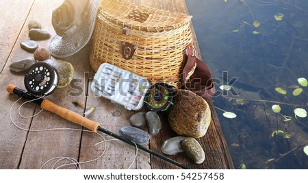 Close-up of fishing equipment and hat at the lake - stock photo