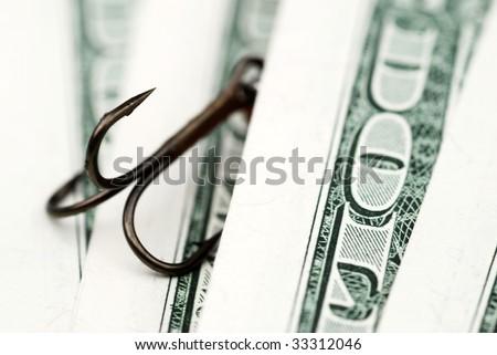 Close-up of fishing hook amongst US dollar bills - stock photo