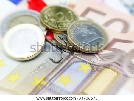 Close-up of fishing hook hidden in Euro currency - stock photo