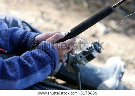 close up of fishing rod and reel in hands