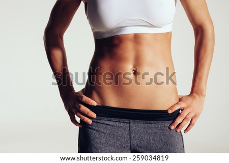 Close up of fit woman's torso with her hands on hips. Female with perfect abdomen muscles on grey background - stock photo