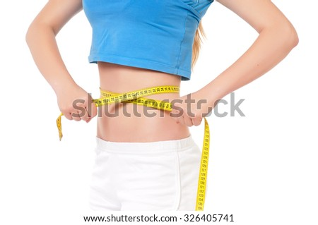 Close up of fitness model with measuring tape - stock photo