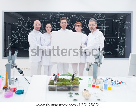 close-up of five smiling  scientists in a chemistry lab holding in hands an empty banner and confident looking in the camera with a blackboard on the background - stock photo
