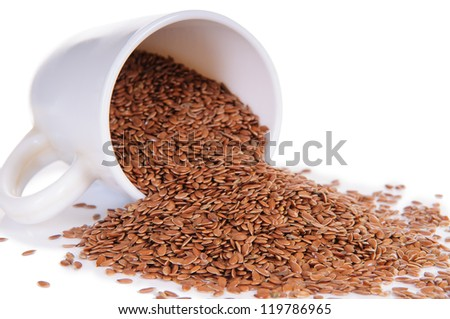 close up of flax seeds in a ceramic cup on white background with clipping path