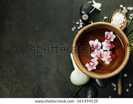 Close up of flowers floating in bowl of water and SPA setting - stock photo
