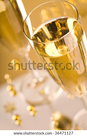 Close-up of flute of champagne over golden background - stock photo