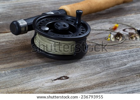 Close up of fly reel, focus on front bottom of reel, with partial cork handled pole and flies blurred out on rustic wooden boards   - stock photo
