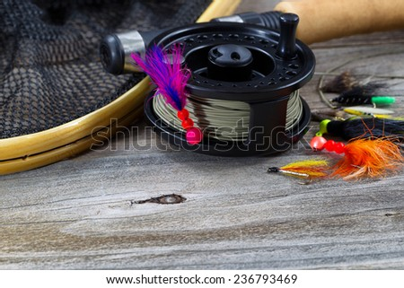 Close up of fly reel, focus on front of reel, with fly jig hanging from spool. Partial cork handled pole, net and flies blurred out on rustic wooden boards  - stock photo