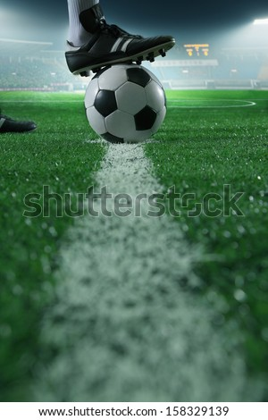 Close up of foot on top of soccer ball on the line - stock photo