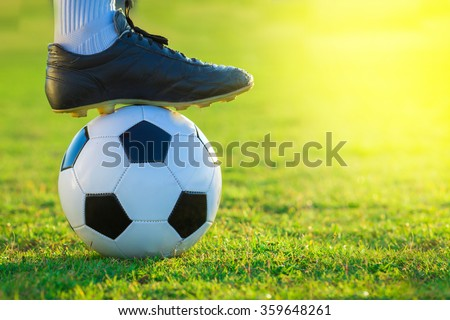 close up of football player tread on the ball on green field - stock photo