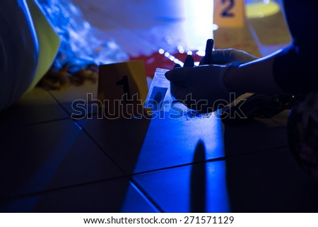 Close-up of forensic scientist preventing evidence of crime - stock photo