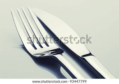 Close-up of fork and knife on light background. Toned image. - stock photo