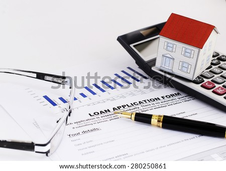 close up of fountain pen and loan application form and paper house on calculator and eyeglasses for Home loans concept