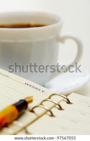 Close-up of fountain pen on notepad at workplace - stock photo