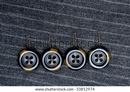 Close up of four buttons on a pin-striped suit jacket - stock photo