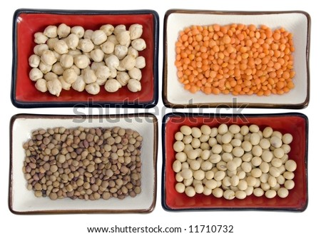 Close up of four dishes with (from up right clockwise): chickpeas, red lentils, soybeans, small lentils. Soft focus. It has a clipping path. - stock photo