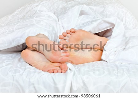 Close up of four feet in a bed - stock photo