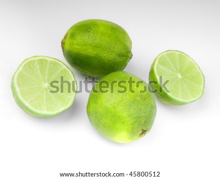 close-up of four lime fruit on gray background