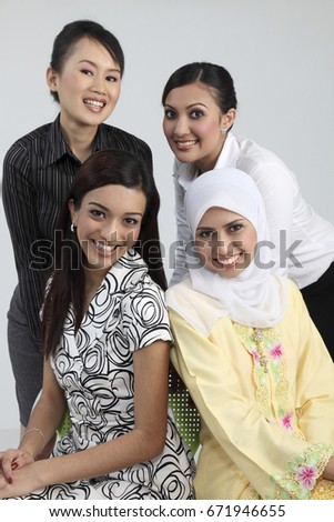 Close up of four women in different races smiling at camera