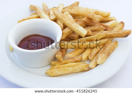 close up of french fries and ketchup in dipping dish on white plate
