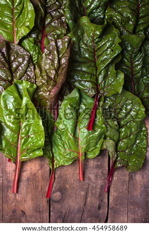 close up of fresh and organic red chard leaves, arranged and spread on a brown, rustic wood background with copy space below, vertical - stock photo