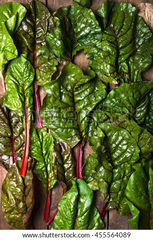 close up of fresh and organic red chard leaves, arranged and spread on a brown, rustic wood background - stock photo