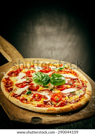 Close Up of Fresh Baked Pizza Topped with Tomatoes, Basil and Cheeses Served on Wooden Pizza Paddle with Dark Grey Background with Copy Space - stock photo