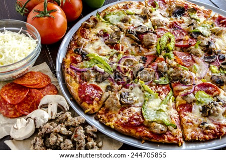 Close up of fresh baked thin crust supreme pizza surrounded by sausage, pepperoni, mushrooms, cheese and tomato ingredients - stock photo