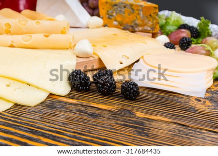 Close Up of Fresh Blackberries, Garnish for Gourmet Cheese Board Appetizer Served on Rustic Wooden Table with Copy Space - stock photo