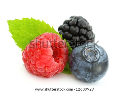 Close-up of fresh blueberry, raspberry, and blackberry with green leaf on white background. Selective focus. - stock photo