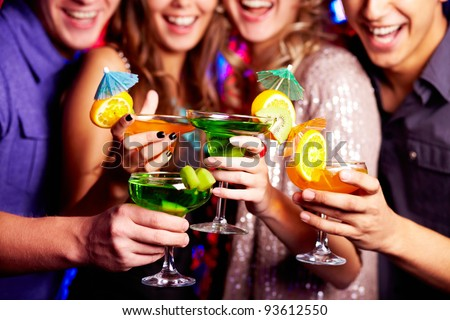 Close-up of fresh cocktails in friends hands - stock photo