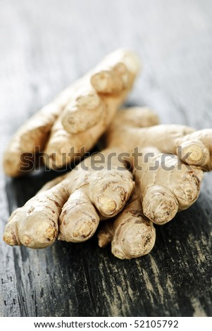 Close up of fresh ginger root spice on wooden table - stock photo