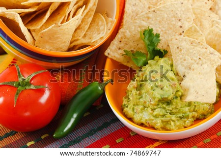 Close up of fresh Guacamole with corn chips, accented with tomato, & jalepeno pepper on a colorful background. - stock photo
