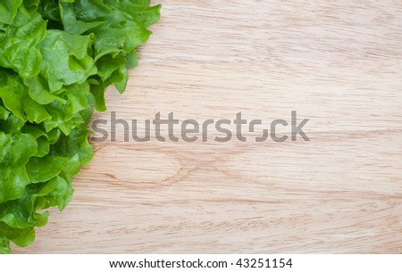 Close up of fresh lettuce on wooden board with empty space for text or design - stock photo