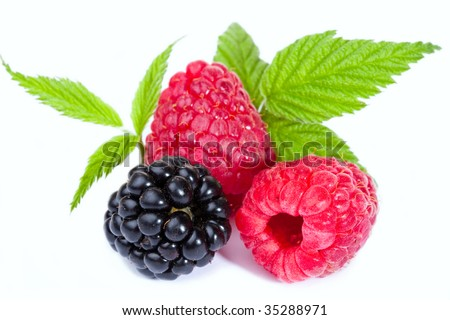 Close-up of fresh raspberries and blackberry with green leaves on white background. - stock photo