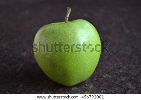 Close up of fresh ripe green apple on dark brown marble kitchen counter. - stock photo
