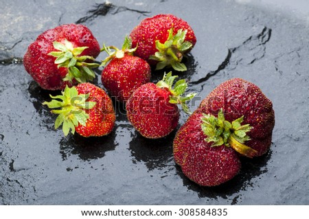 Close up of fresh ripe strawberries on black stone background - stock photo