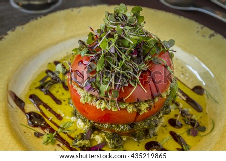 Close up of fresh tomato tower filled with olive tapenade sitting on ricotta cheese, balsamic vinegar and olive oil and garnished with microgreens sitting on rustic yellow plate - stock photo