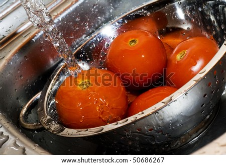 Close-up of fresh tomatos in silver strainer and running water - stock photo