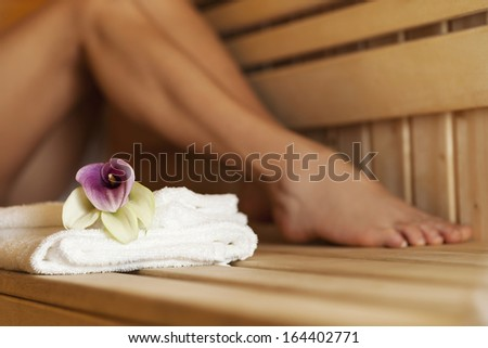 Close up of fresh towels and flowers in sauna  - stock photo