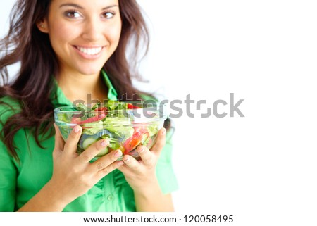Close-up of fresh vegetable salad in glass bowl held by pretty young girl