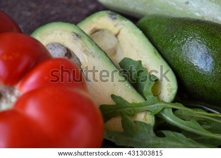 Close up of fresh vegetables. Avocado, a part of red ripe tomato and green arugula. - stock photo